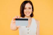 selektivní zaměření usměvavé elegantní dívky držící kreditní kartu izolovaná na žluté