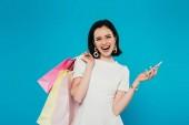 vzrušená elegantní žena v šatech s nákupními sáčky, které drží smartphone izolované na modré