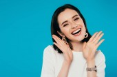 mosolygó elegáns nő ruhában, kézzel az arc közelében izolált kék