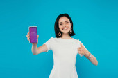 KYIV, UKRAINE - JULY 3, 2019: smiling elegant woman in dress holding smartphone with Instagram logo and showing thumb up isolated on blue