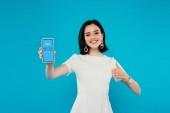 Kiew, Ukraine - 3. Juli 2019: lächelnde elegante Frau im Kleid halten Smartphone mit Skype-Logo und zeigt Daumen nach oben isoliert auf blau
