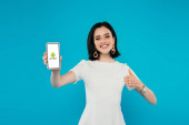 KYIV, UKRAINE - JULY 3, 2019: smiling elegant woman in dress holding smartphone with android logo and showing thumb up isolated on blue