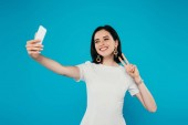 smiling elegant woman in dress taking selfie and showing peace sign isolated on blue