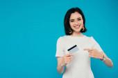 usměvavá elegantní žena v šatech ukazujícími prstem na kreditní kartu izolovaná na modré