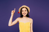smiling girl in straw hat showing idea gesture isolated on purple