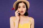 ragazza scioccata in cappello di paglia parlando sullo smartphone isolato su viola