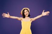 usmívající se krásná dívka v slaměném klobouku s otevřenou náručí izolovaná na purpurové