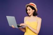 šokovaná usměvavá dívka v slaměném klobouku držící přenosný počítač izolovaný na fialový