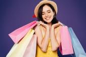 usmívající se dívka v slaměném klobouku se zavřenýma očima, držící nákupní tašky izolovaná na purpurové