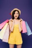izgatott mosolygós lány Szalmakalapot a bevásárló táskák izolált lila