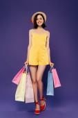 teljes hosszában véve a mosolygó lány Szalmakalapot a bevásárló táskák elszigetelt lila