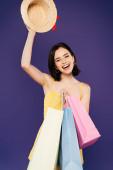 mosolyogva lány bevásárló táskák gazdaság Szalmakalapot izolált lila