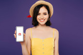 KYIV, UKRAINE - JULY 3, 2019: smiling girl in straw hat holding smartphone with huawe logo isolated on purple