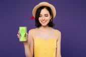 usměvavá dívka v slaměném klobouku držící telefon Smartphone s beat Shopping App izolovaný na fialový