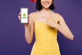 Kijev, Ukrajna-július 3, 2019: vágott kilátás lány Szalmakalapot mutat ujját a smartphone az Android logó izolált lila