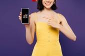 Kyjev, Ukrajina-3. července 2019: oříznutý pohled dívky v slaměném klobouku ukazujícími prstem na smartphone s Deezer aplikací izolované na purpurové
