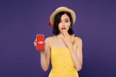 KYIV, UKRAINE - JULY 3, 2019: girl in straw hat showing idea gesture and holding smartphone with youtube logo isolated on purple
