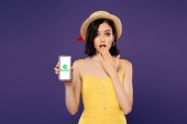 KYIV, UKRAINE - JULY 3, 2019: girl in straw hat showing idea gesture and holding smartphone with Spotify logo isolated on purple