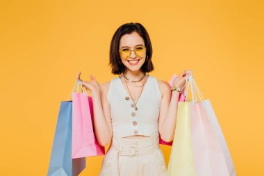 smiling woman in sunglasses holding shopping bags isolated on yellow