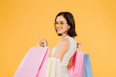smiling happy woman in sunglasses holding shopping bags isolated on yellow
