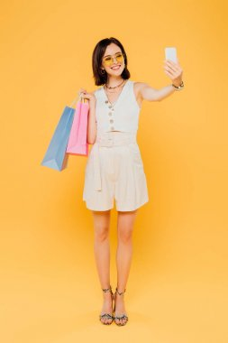 Full length view of happy fashionable girl in sunglasses with shopping bags taking selfie on smartphone isolated on yellow stock vector