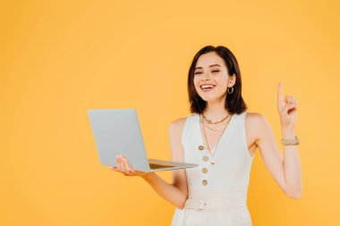 Smiling elegant girl with laptop showing idea gesture isolated on yellow stock vector