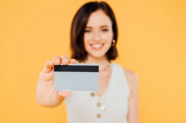 Selective focus of smiling elegant girl holding credit card isolated on yellow stock vector