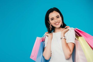 smiling elegant woman in dress with shopping bags isolated on blue