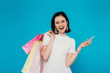mavi izole akıllı telefon tutan alışveriş çantaları ile elbise heyecanlı zarif kadın
