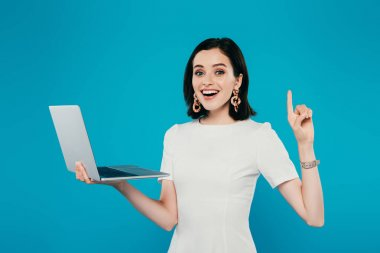 Excited smiling elegant woman holding laptop and showing idea gesture isolated on blue stock vector