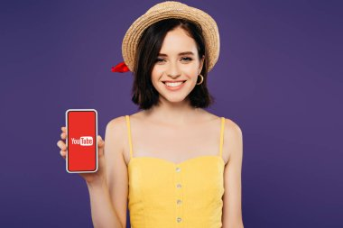 KYIV, UKRAINE - JULY 3, 2019: smiling girl in straw hat holding smartphone with youtube app isolated on purple stock vector