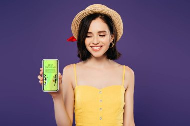 Smiling girl in straw hat holding smartphone with beat shopping app isolated on purple stock vector