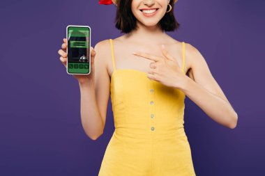 Cropped view of girl in straw hat pointing with finger at smartphone with booking app isolated on purple stock vector