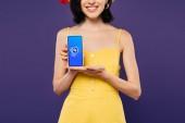 Kyjev, Ukrajina-3. červenec 2019: oříznutý pohled na usmívající se dívku držící smartphone se Shazam aplikace izolované na purpurové
