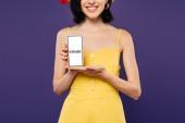 kyiv, ukraine - 3. Juli 2019: abgeschnittene Ansicht eines lächelnden Mädchens mit Smartphone und Zunder-App isoliert auf lila