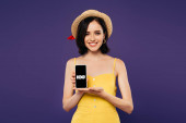 KYIV, UKRAINE - JULY 3, 2019: smiling pretty girl in straw hat holding smartphone with HBO app isolated on purple