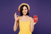 KYIV, UKRAINE - JULY 3, 2019: smiling pretty girl in straw hat holding smartphone with Youtube app and showing ok sign isolated on purple