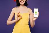 kyiv, Ukraine - 3. Juli 2019: abgeschnittene Ansicht eines lächelnden Mädchens, das ein Smartphone mit Android-Logo in der Hand hält und Ok-Zeichen zeigt, isoliert auf lila