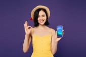 usmívající se krásná dívka v slaměném klobouku přidržující telefon Smartphone s rezervacemi a ukazující na OK nápis izolovaný na purpurovém