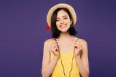 lächelnd hübsche Mädchen in Strohhut hält Kopfhörer isoliert auf lila