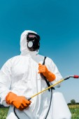exterminator in orange latex gloves holding toxic spray against sky