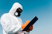 Mann in Schutzmaske und Uniform schreibt und hält Klemmbrett