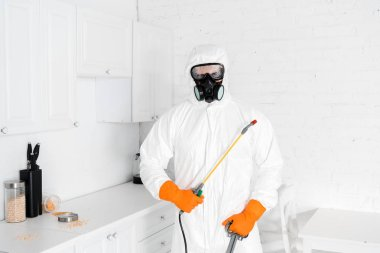 exterminator in protective mask and uniform holding toxic equipment near kitchen cabinet