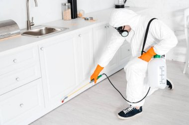 exterminator holding toxic equipment near kitchen cabinet