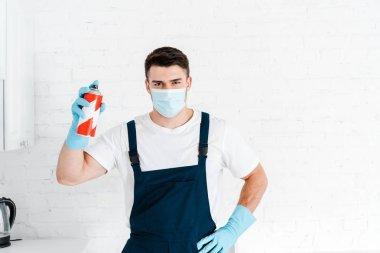 exterminator in latex gloves holding toxic spray can and standing with hand on hip