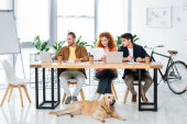 three friends using laptop and doing paperwork in office
