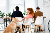 Rückansicht von drei Freunden, die am Tisch sitzen und Golden Retriever füttern