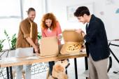 tři usměvavé fiendy s krabic s pizzou v kanceláři