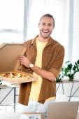 Fotografie pohledný a usměvavý obchodník držící krabici s pizzou v kanceláři
