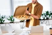 Fotografia vista ritagliata di uomo daffari che tiene scatola con pizza in ufficio